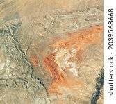 Desert land on satellite photo, aerial top view of Earth surface as abstract texture background. Nature pattern, deserted landscape taken from space. Elements of this image furnished by NASA.