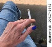 macro photo cigarette in hand.... | Shutterstock . vector #2041749992