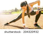 Stock photo young sportswoman stretching and preparing to run 204320932