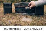 Small photo of There is an old retro tape recorder on the grass. Man takes a tape cassette out of case inserts it into the tape recorder. Concept of old school vintage technique of the last century