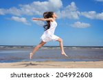 happy woman jumping on the beach | Shutterstock . vector #204992608