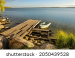 A Wooden Pier On A Lake With A...
