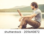 Young Man Reading Book Outdoor...