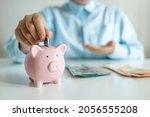 woman's hand putting a coin... | Shutterstock . vector #2056555208