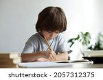Small photo of Solicitous, attentive, diligent 6 years old schoolboy learning to write and draw from home. Cute pupil kid sitting at desk doing homework for preschool children education.