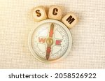 Small photo of Business concept. On the table is a compass and cubes with the inscription - SCM