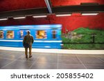 Small photo of STOCKHOLM, SWEDEN - JUNE 10, 2014: Train arrives Solna Centrum metro station on June 10, 2014 in Stockholm, Sweden. This station was painted in 1975 by artists Anders Aberg and Karl-Olov Bjork.