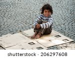 Small photo of TIRANA, ALBANIA, MAY 14, 2010 - Unknown homeless kid sitting on the old box on the street in Tirana