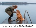 Handsome caucasian girl caress brown Nova Scotia Duck Tolling Retriever. Woman with pet sitting on pier on lake and look into each other eyes. Female travelling with dog. Selective focus. Dog loyalty.