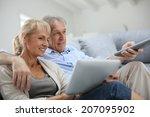 Senior Couple Sitting In Sofa...