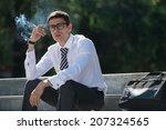 Well dressed business man smoking sitting on a street sidewalk