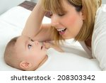 mother leaning over her little... | Shutterstock . vector #208303342