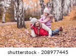 mom walks in autumn park with... | Shutterstock . vector #208977445