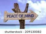 Small photo of Peace of Mind wooden sign with a beach on background