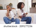 Small photo of Unhappy couple arguing on the couch at home in the living room