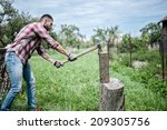 Athletic Man Splitting Wood An...