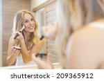 Blonde beautiful woman doing makeup in front of mirror