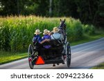 Small photo of Three young Amish men in open buggy going down country road in rural Pennsylvania.