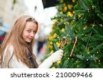Girl decorating Christmas tree with colorful candies - stock photo
