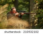 hunter with his rifle in spring ... | Shutterstock . vector #210532102