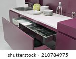 Stock photo close up of open red furniture in the modern kitchen with dishes on the worktop 210784975