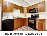 Stock photo kitchen cabinets with black appliances and white tile wall trim 211811665