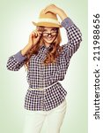 Small photo of portrait of a cute young woman with casual garb looking over her glasses and smile. studio shot.