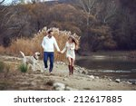 Stock photo young happy couple walking with dog near the lake in autumn 212617885