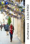 Girl walking on a Parisian street decorated for Christmas - stock photo