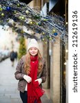Girl walking on a Parisian street brightly decorated for Christmas - stock photo
