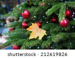 Yellow autumn leaf fallen on a branch of decorated Christmas tree on a Parisian street - stock photo