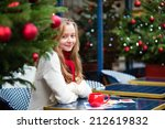 Smiling girl with greeting cards in a Parisian cafe - stock photo