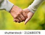 Elderly Couple Holding Hands...