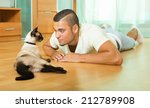 Stock photo guy playing with siamese kitten at home 212789908
