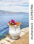 Colourful pink and white flowers in white clay pot overlooking the Saronic Gulf in Hydra island in the Aegean Sea, Greece. - stock photo
