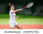 Young Tennis Player Hitting...
