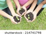 hands holding sapling in soil... | Shutterstock . vector #214741798