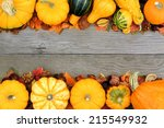 Autumn border of pumpkins and vegetables over a wood background                 - stock photo