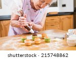 old woman making and decorating ... | Shutterstock . vector #215748862