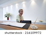 receptionist behind desk with... | Shutterstock . vector #216109972