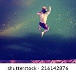 a boy jumping of an old train... | Shutterstock . vector #216142876