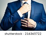 businessman in blue suit tying...