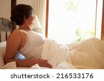 woman waking up in bed in... | Shutterstock . vector #216533176