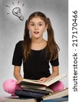 Small photo of Kids learn. Portrait intelligent surprised girl came up with idea reading book aha, isolated background with lighting bulb. Positive human emotions, facial expressions, perception. Education concept