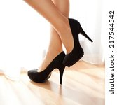 Small photo of Female legs on a high heels. Standing by the window.