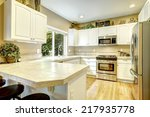 Stock photo white kitchen cabinets with steel appliances and light tone hardwood floor 217935778