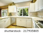 Stock photo white kitchen cabinets with steel appliances and light tone hardwood floor 217935805