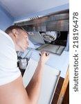 young repairman fixing a broken ... | Shutterstock . vector #218196478