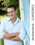 Small photo of Smiling 40-year-old man leaning on home wall