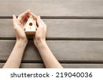 woman holding tiny wooden house | Shutterstock . vector #219040036